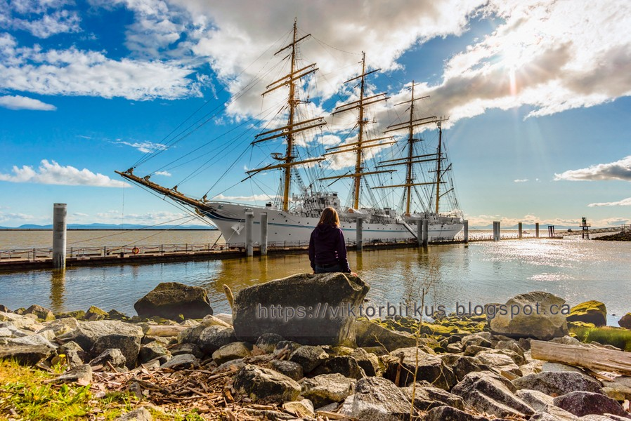 www.viktorbirkus.blogspot.ca - girl sits on a rock and looks at the big white sailing ship moored to the pier - The girl sits on a rock and looks at the big white sailing ship moored to the pier, the blue sky and the rays of the sun making their way thr... - protected by IMATAG