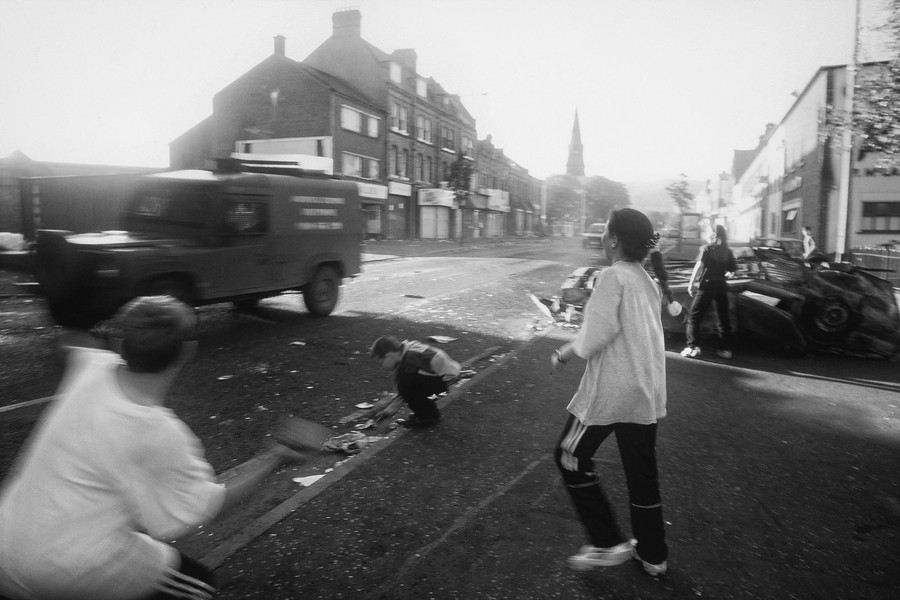 © Jean Pierre Porcher - A15_1-Editar.jpg - NORTHERN IRELAND (Belfast) 07/1996 Young catholics throwing stones on britanic jeep in Ardoyn ghetto.  To the south of Ardoyne there are a nu... - protected by IMATAG