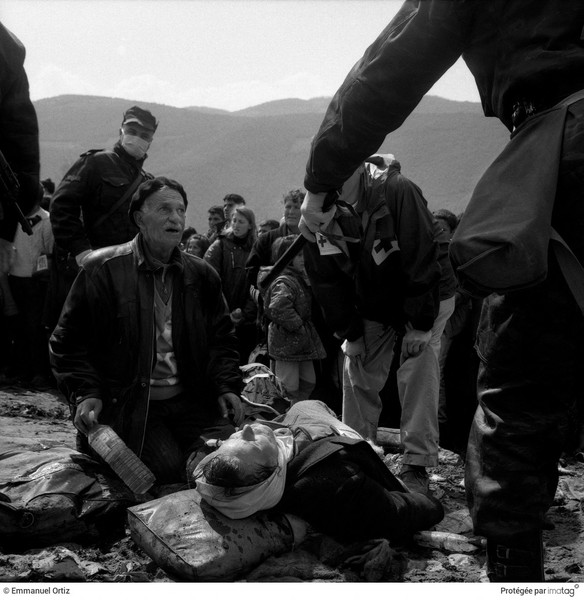 © Emmanuel Ortiz - BALKANS EN GUERRE - 1998 , Macedonia : For fear of an out break of disease,Macedonian police wear masks and gloves as they try to keep the tide of refugees moving … - protected by IMATAG