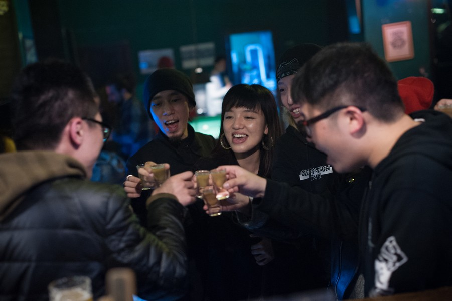 Julien Hazemann - PUNKS AND MIN GONGS, TOGETHER AT THE « NUTS »  - Members of the Nuts family, the mythical underground club of Chongqing, raising a glass. The young people who attend the club come from diver... - protected by IMATAG