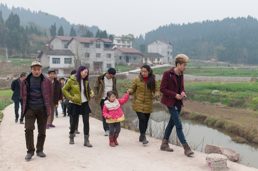 Julien Hazemann - THE VILLAGE OF THE MIN GONG - He Long (right) walks with his parents and daughter through his native village. Hairdresser in Chongqing, he returned to the village for the ... - protected by IMATAG