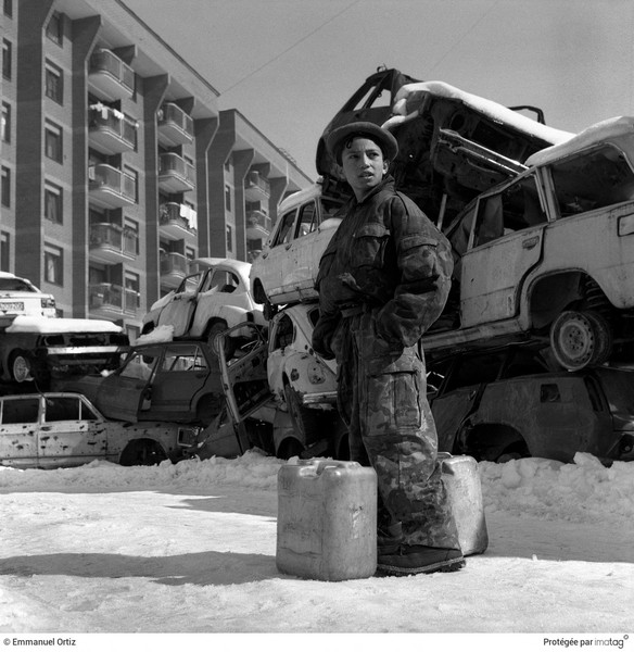 Emmanuel Ortiz - BALKANS EN GUERRE - 1994,Bosnia-Herzegovina , Sarajevo : A young boy takes a rest from carrying water home.A barricade of old cars protects him from sniper fire. - protected by IMATAG