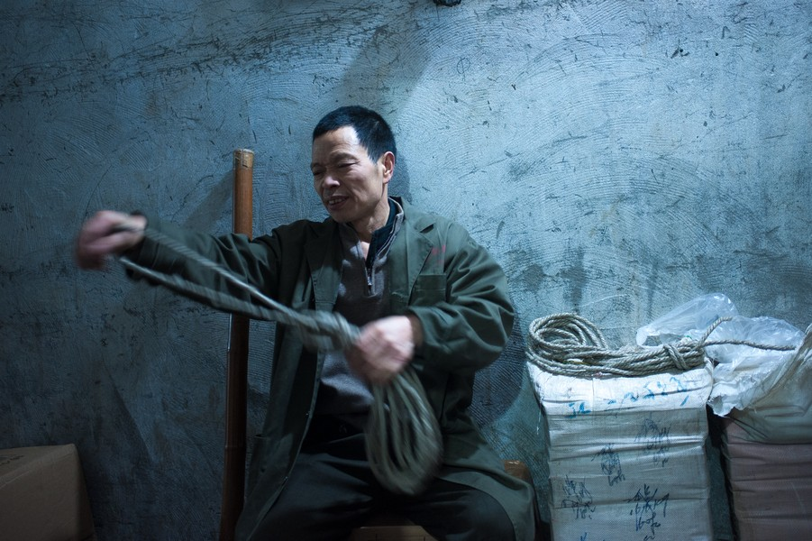 """Julien Hazemann - THE BANG OF THE MIN GONG - Li Wenyin preparing his """"bang"""", the bamboo stick he uses to transport goods, in the underground warehouse of Li Wuhua, his main customer for ... - protected by IMATAG"""
