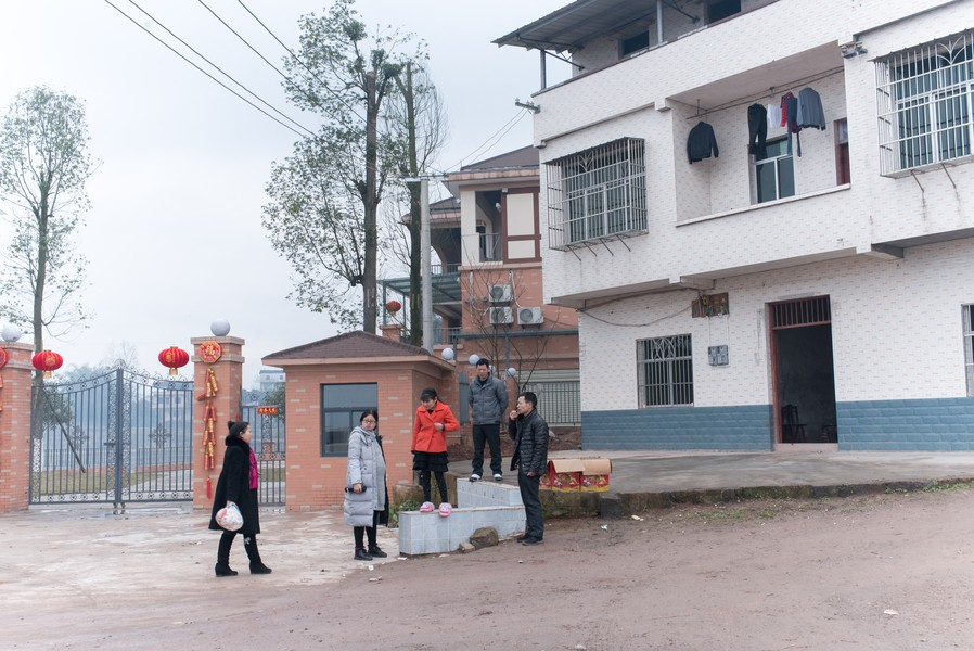 Julien Hazemann - THE NEW HOUSE OF THE MIN GONG - Li Wenyin and members of his family in Guangan, his native village, standing on the front steps of the house, that he had reconstructed with ... - protected by IMATAG
