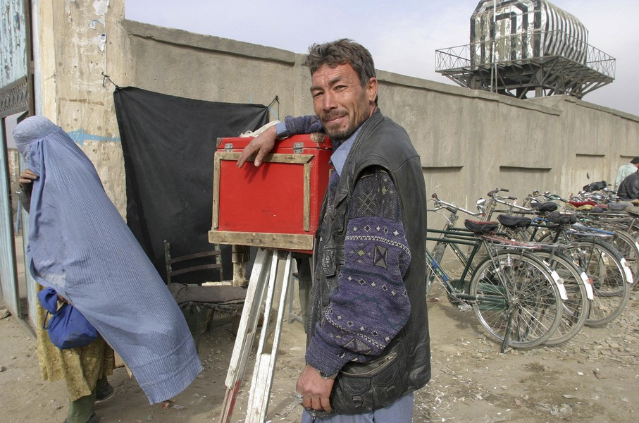 © Jean Pierre Porcher - F15_1.jpg - AFGHANISTAN (Kabul) 12/2005 Photographe devant le Ministry of Martyrs and Disabled (MMD). Il réalise les photos d'identité pour constituer un... - protected by IMATAG