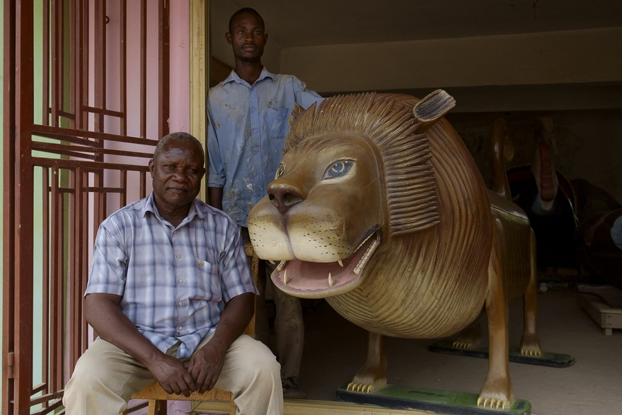 Thierry Secretan - PAA JOE & SON JACOB COFFIN MAKERS IN GHANA - Paa Joe and his son Jacob, master coffin makers in Accra, Ghana, next to a lion coffin, one of Paa Joe's most famous type of coffin usually u... - protected by IMATAG