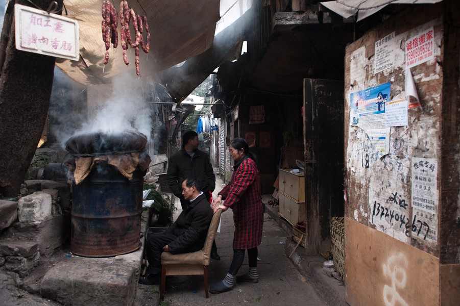 Julien Hazemann - THE AGONY OF SHI BA TI  - Three of the last inhabitants of the Shi Ba Ti district smoking sausages during the Chinese New Year's celebrations, in 2013. Shi Ba Ti was t... - protected by IMATAG