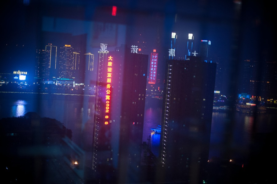 Julien Hazemann - THE VIEW OF THE MIN GONG  - View on the Yangtze River at night from Li Wenyin's apartment. Wenyin's neighborhood is undergoing a deep transformation, and an increasing g... - protected by IMATAG