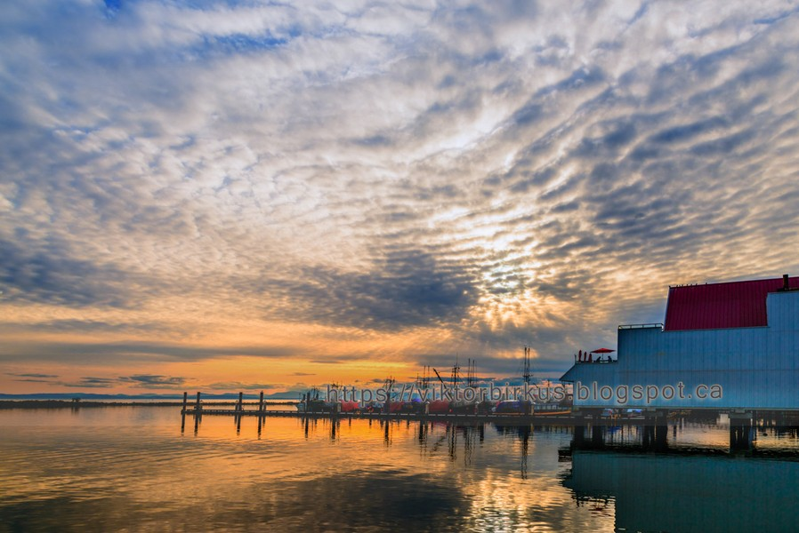 www.viktorbirkus.blogspot.ca - Sunset on the river near the pier of fishing ships with reflection - Sunset on the river near the pier of fishing ships with reflection in the water, huge cloudy sky and silhouettes of people under a canopy in ... - protected by IMATAG
